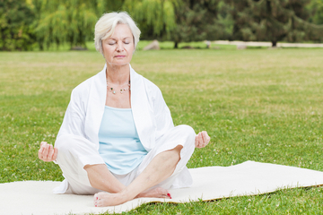 Older woman meditating in a park